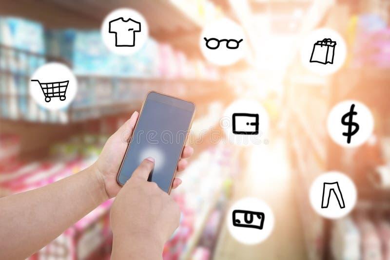 De vrouwen gebruiken mobiele telefoon en vaag beeld van supermarkt met ico stock fotografie
