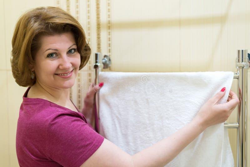 De vrouwen hangen handdoek op verwarmd handdoekspoor stock afbeelding
