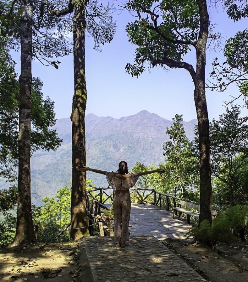 De vrouwen heffen hun wapens Achtergrondbomen en bergen in Nern Chang Puak View Point, Kanchanaburi, Thailand op stock afbeeldingen