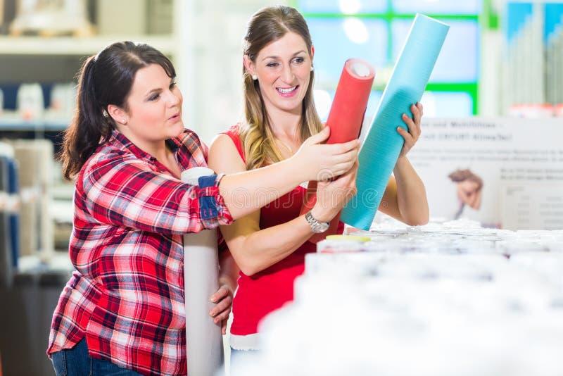 De vrouwen in het huisverbetering slaan het kiezen van behang op stock foto's