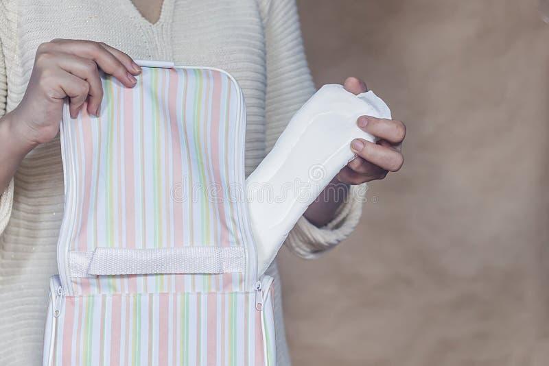 De vrouwen houden een menstrueel stootkussen Jonge vrouw die een sanitair stootkussen van haar zak nemen Wit menstrueel stootkuss royalty-vrije stock afbeelding