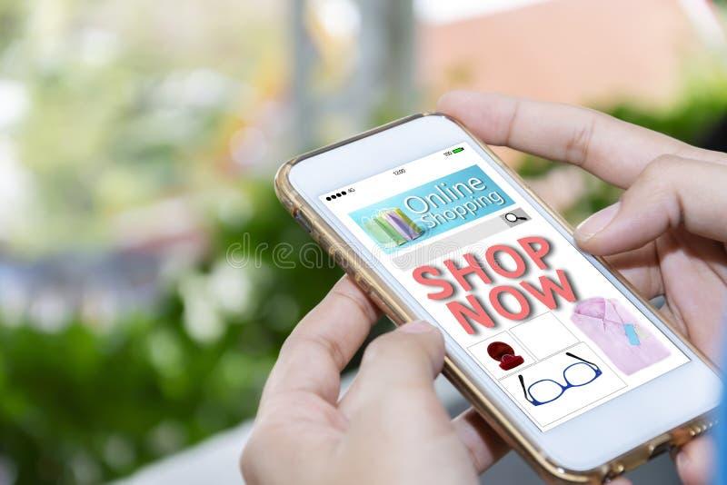De vrouwen houden een smartphone Website online het winkelen concept stock afbeeldingen