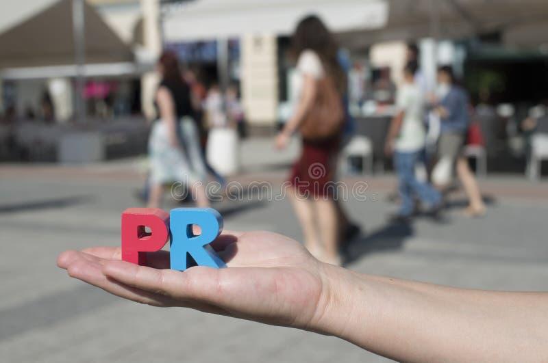 De vrouwen houden houten brieven PR stock afbeelding
