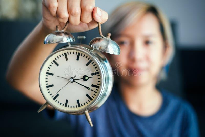 De vrouwen houden klok in hand stock fotografie