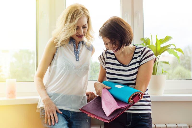De vrouwen letten op steekproeven van stoffen voor gordijnen, meubilair upholste stock fotografie