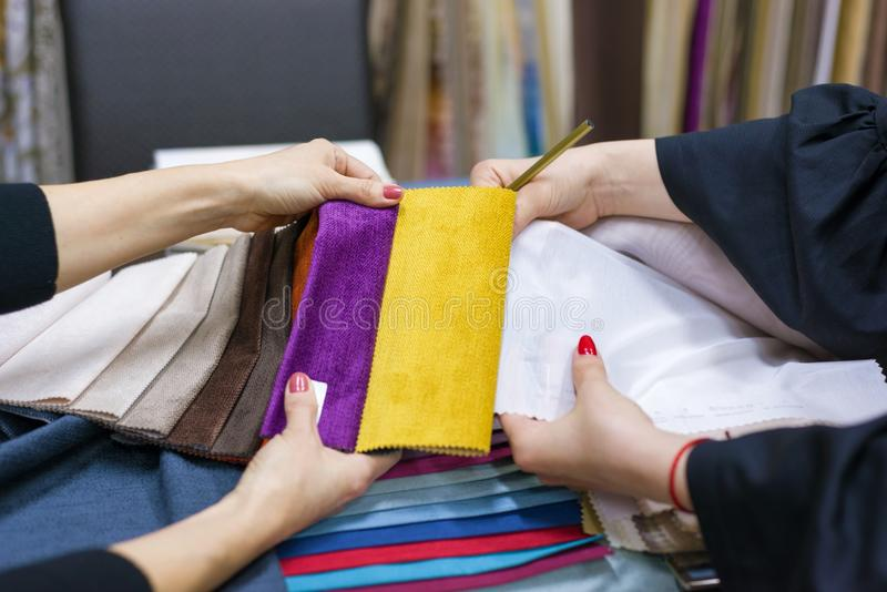 De vrouwen letten op steekproeven van stoffen voor gordijnen, meubilairstoffering in een nieuw huis royalty-vrije stock foto's