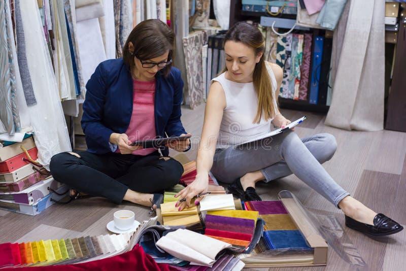 De vrouwen letten op steekproeven van stoffen voor gordijnen, meubilairstoffering in een nieuw huis stock afbeelding