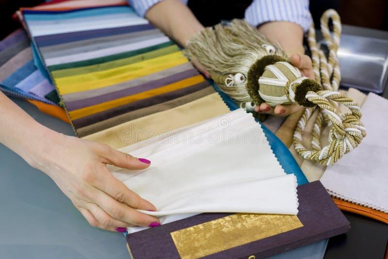 De vrouwen letten op steekproeven van stoffen voor gordijnen, meubilairstoffering in een nieuw huis stock foto