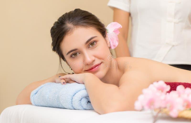De vrouwen ligt op het bed klaar om kuuroordcursus met de Massagetherapeut over te nemen stock foto