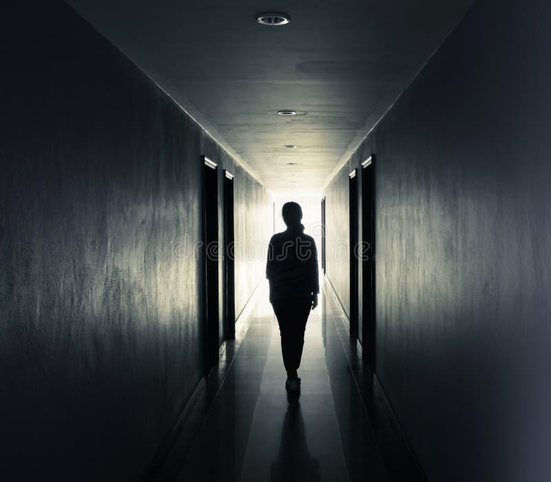 De vrouwen lopen alleen in dark royalty-vrije stock afbeeldingen
