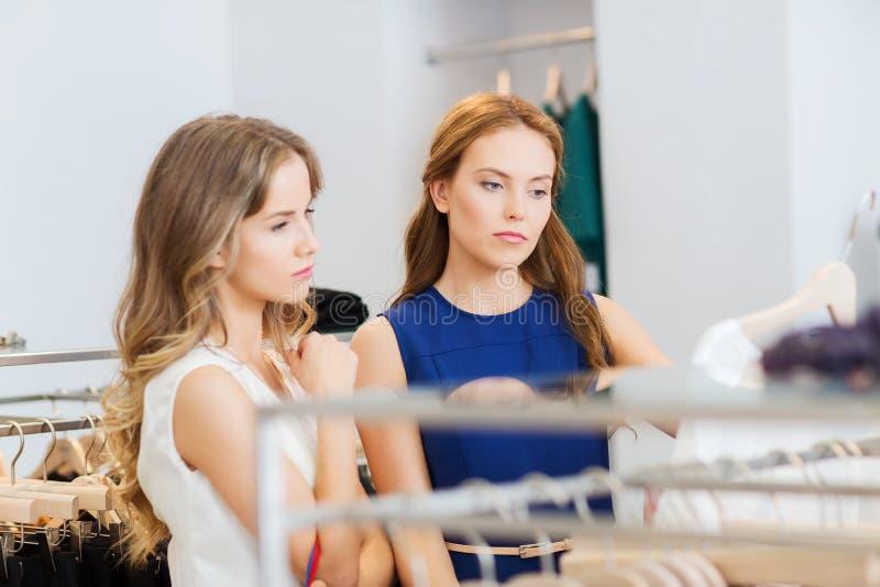 De vrouwen met het winkelen zakken bij kleding winkelen royalty-vrije stock afbeelding