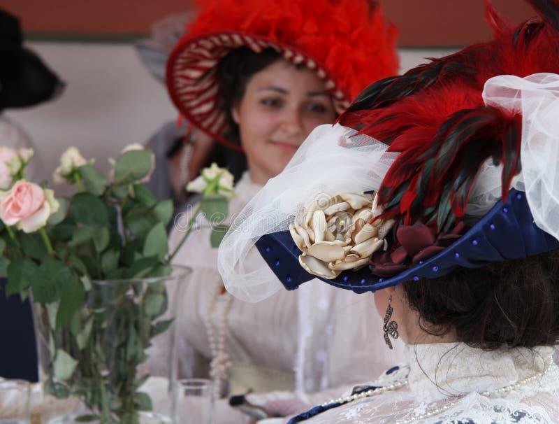 De vrouwen in mooie uitstekende stijlhoeden met veer spreken royalty-vrije stock foto's