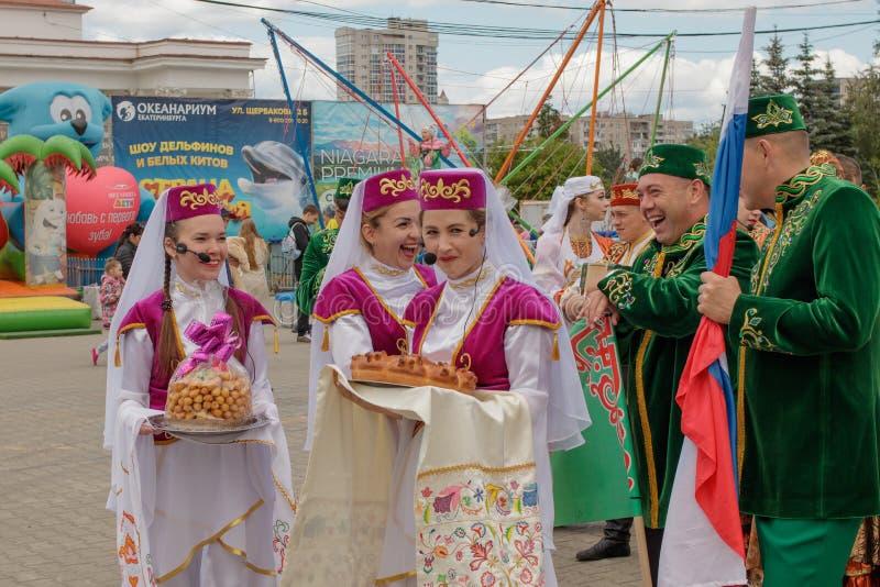 De vrouwen in nationale kleren houden Tatar schotels in hun handen stock fotografie