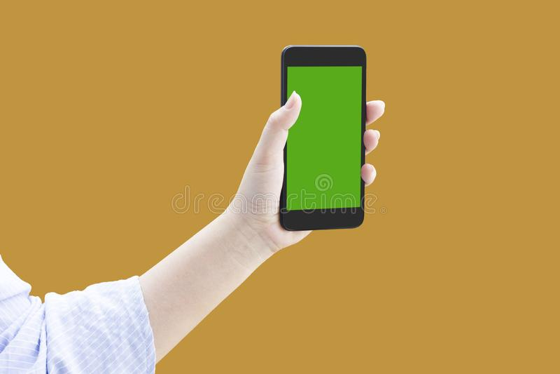 de vrouwen overhandigen greep of tonen of stellen smartphone of mobiele telefoon of cellphone met het knippen van weg op oranje a stock foto's