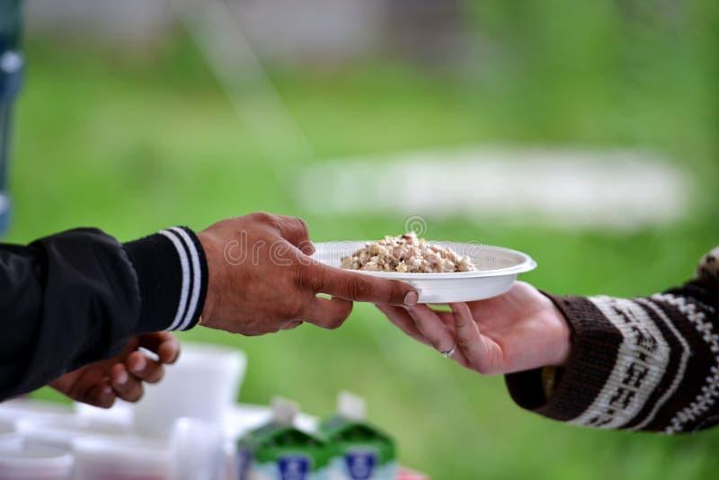 De vrouwen overhandigen het dienen van een andere persoon een plaat met voedsel royalty-vrije stock afbeelding