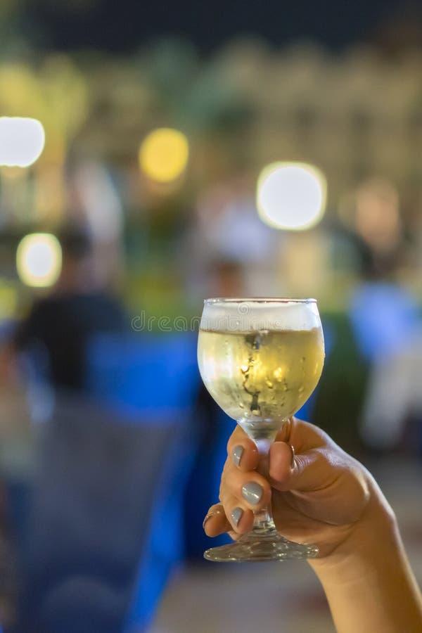 De vrouwen overhandigen het houden van een glas witte wijn close-up gestemd, viering Verticale foto stock afbeeldingen