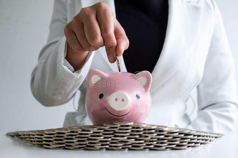 De vrouwen overhandigen het zetten van muntstuk in roze de besparingsgeld van het spaarvarken met muntstukkenbunker stock afbeelding