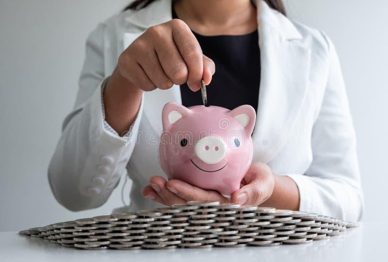 De vrouwen overhandigen het zetten van muntstuk in roze de besparingsgeld van het spaarvarken met muntstukkenbunker royalty-vrije stock foto