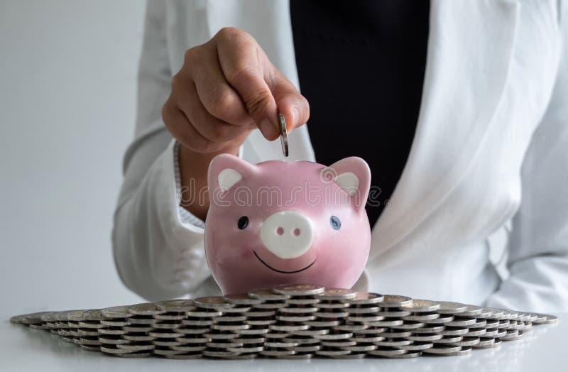 De vrouwen overhandigen het zetten van muntstuk in roze de besparingsgeld van het spaarvarken met muntstukkenbunker stock afbeeldingen