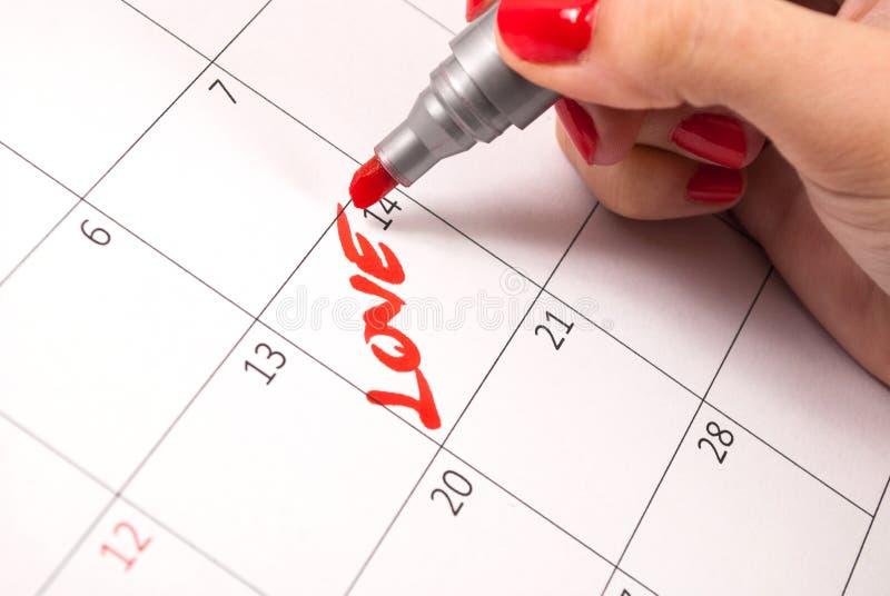 De vrouwen overhandigen met de liefdewoord van de potloodtekening in kalender voor Valentijnskaartendag stock foto's