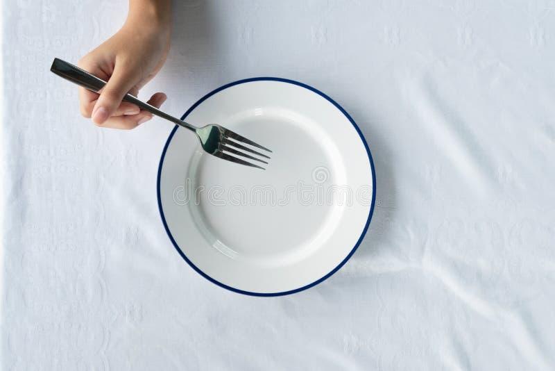 De vrouwen overhandigen de vork van het holdingsmetaal voor voedsel etend met lege witte blauwe emailschotel op achtergrond van h stock foto's