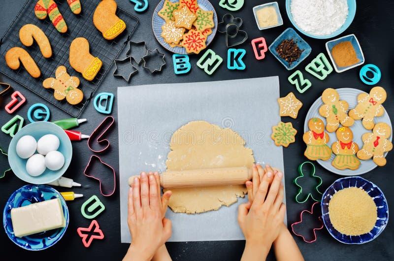 De vrouwen ` s en de kinderen` s handen ontwikkelen gemberdeeg met ingredie stock afbeelding