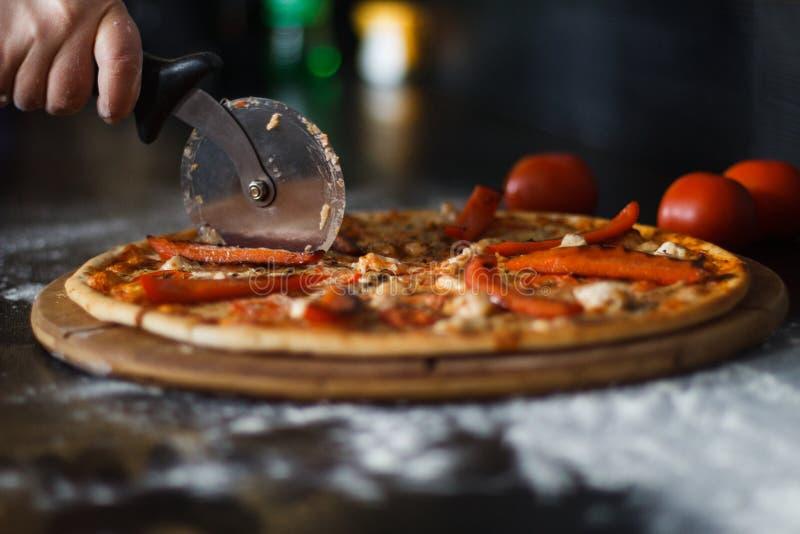 De vrouwen` s hand met een mes sneed de pizza op zwart close-up als achtergrond stock foto's