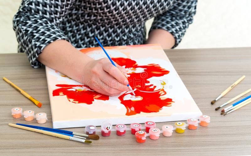 De vrouwen` s hand trekt het schilderen met een borstel en verven stock foto