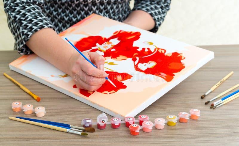 De vrouwen` s hand trekt het schilderen met een borstel en verven stock fotografie