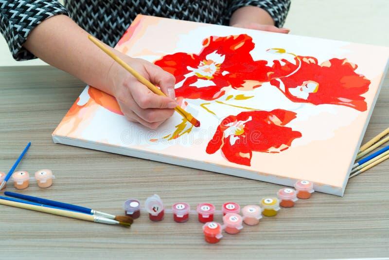 De vrouwen` s hand trekt het schilderen met een borstel en verven stock foto's