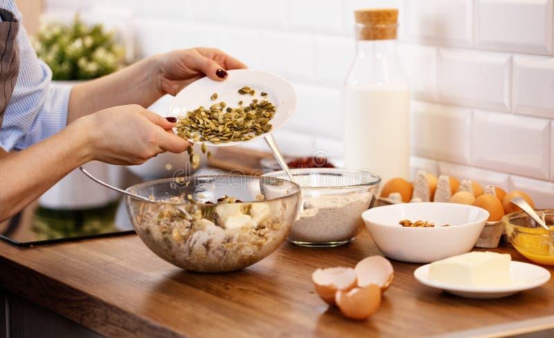 De vrouwen` s handen bereiden deeg met noten en zaden voor koekjes voor royalty-vrije stock foto's