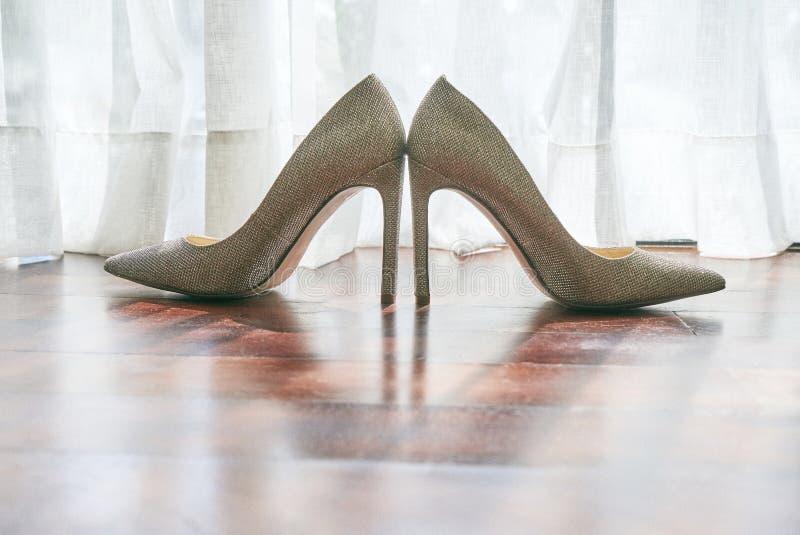 De vrouwen` s schoenen op de houten vloer, het zonlicht achter het witte gordijn, de schaduw van de schoenen op de vloer - lage h stock fotografie