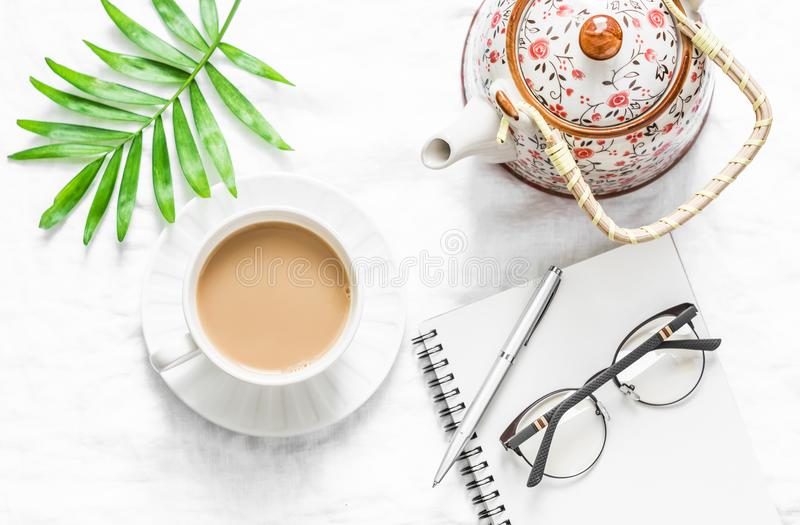De vrouwen` s vlakte legt lijst met een kop van melkthee, theepot en maakt leeg notitieboekje op een lichte achtergrond schoon, h royalty-vrije stock foto's
