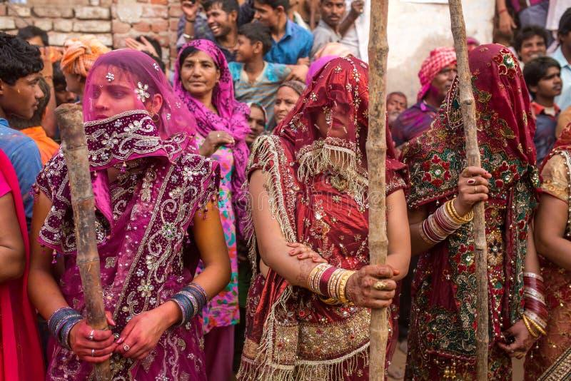 De vrouwen slaan omhoog mannen met lange stokken als ritueel in de viering van Lathmar Holi in Nandgaon stock afbeeldingen