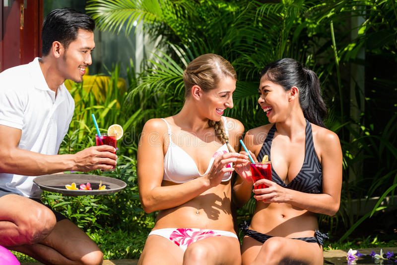 De vrouwen in vakantie bij Aziatisch hotel voegen met cocktails samen stock afbeelding
