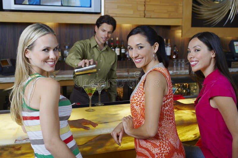 De Vrouwen van barmanpouring drinks for bij Bar royalty-vrije stock afbeelding