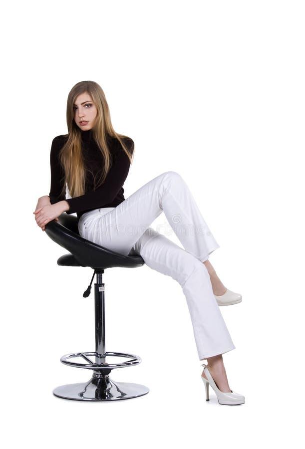 De vrouwen van de manier zitten op de stoel stock foto's