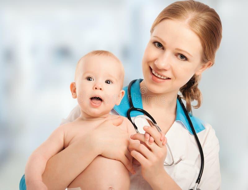 De vrouw van de pediater arts die geduldige baby houden royalty-vrije stock foto's
