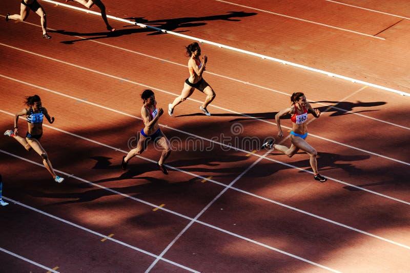 de vrouwen van groepsagenten stellen sprintrace bij stadion in werking stock foto's