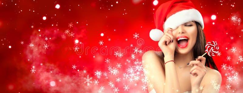De vrouwen van de kerstman met zakken Blij modelmeisje in de hoed van de Kerstman met rode lippen en lollysuikergoed in haar hand royalty-vrije stock afbeeldingen