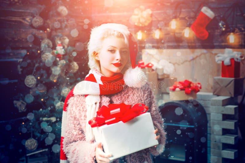 De vrouwen van de kerstman met zakken Blonde vrouwelijk model gekleed in een Santa Claus-hoed Leuke jonge vrouw met santahoed Mag royalty-vrije stock fotografie