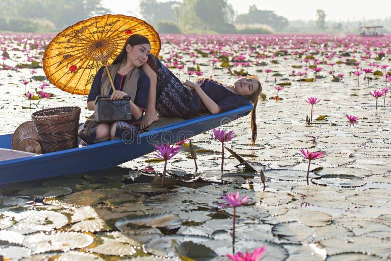 De vrouwen van Laos in het meer van de bloemlotusbloem, Vrouw die traditionele Thaise mensen, Rode Lotus Sea UdonThani Thailand d stock foto