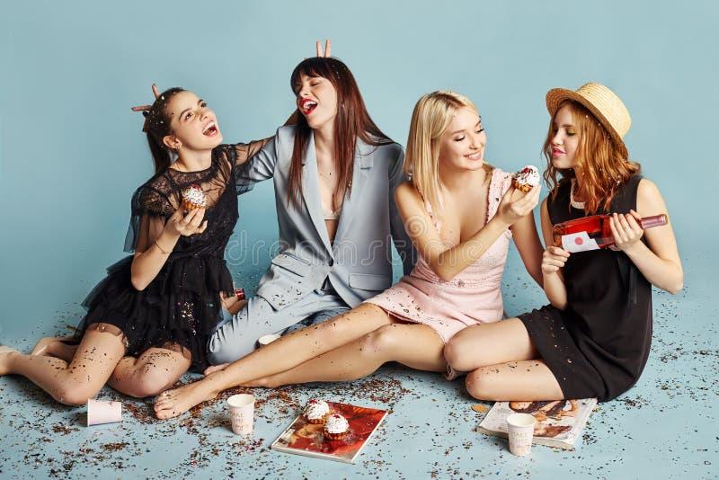 De vrouwen vieren de vakantiepartij die pret hebben die en cakes eten onder de vliegende confettien lachen En meisjes die stellen stock afbeelding
