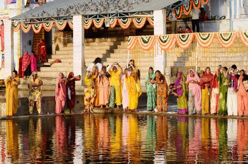 de vrouwen voeren puja - rituele ceremonie bij het heilige meer van Pushkar Sarovar, India uit stock afbeelding