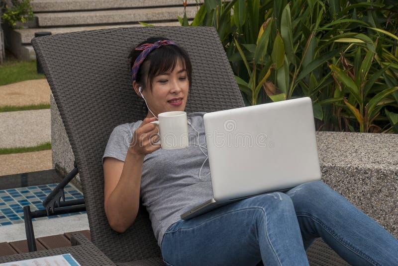 De vrouwen werken met laptops aan het bed door de pool stock fotografie