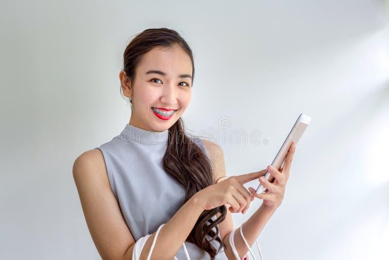 De vrouwen winkelen door mobiele toepassingen Gelukkige jonge Vrouwelijke holding het winkelen zakken en mobiele telefoon Verrich royalty-vrije stock foto's