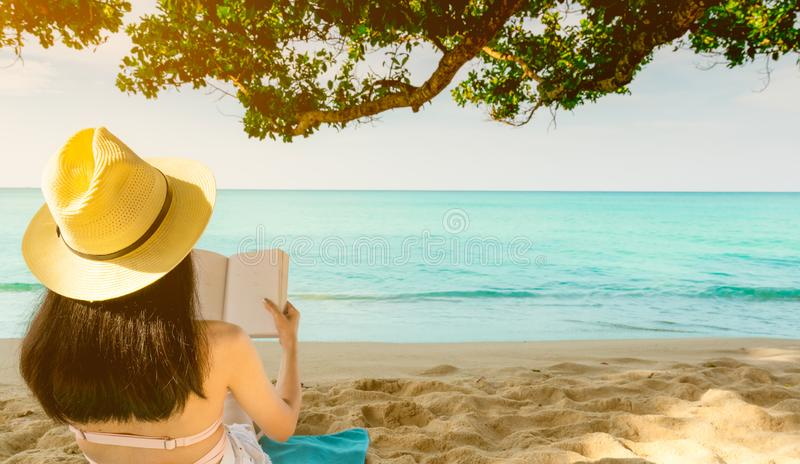De vrouwen zitten en lezing een boek onder de boom bij kust Achtermening van sexy Aziatische vrouw met strohoed die en van vakant stock fotografie