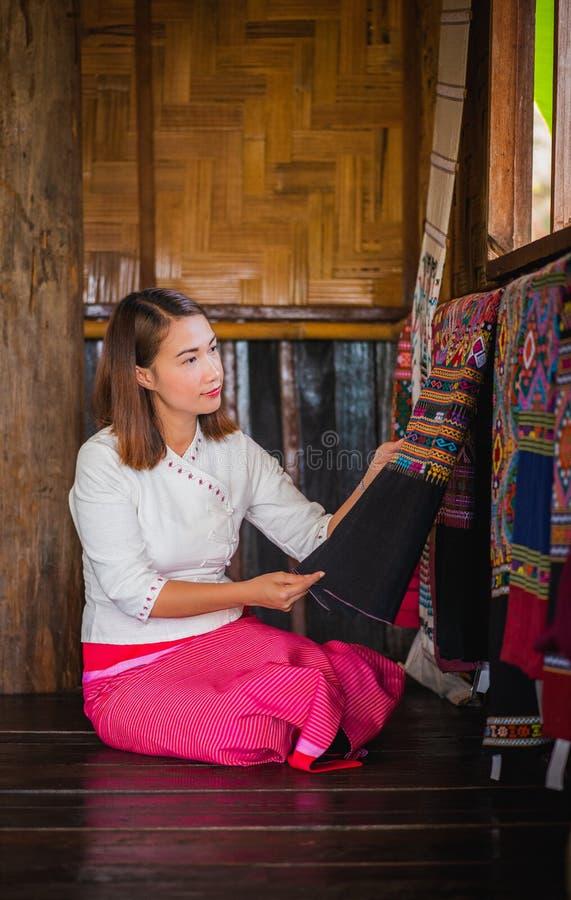 De vrouwen zitten het letten van op het mooie stof Hangen tonen in winkel bij Pua-district stock foto's