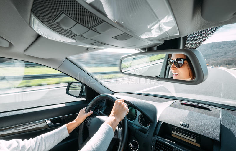 De vrouwenaandrijving een auto denkt in achtermeningsspiegel na stock afbeeldingen