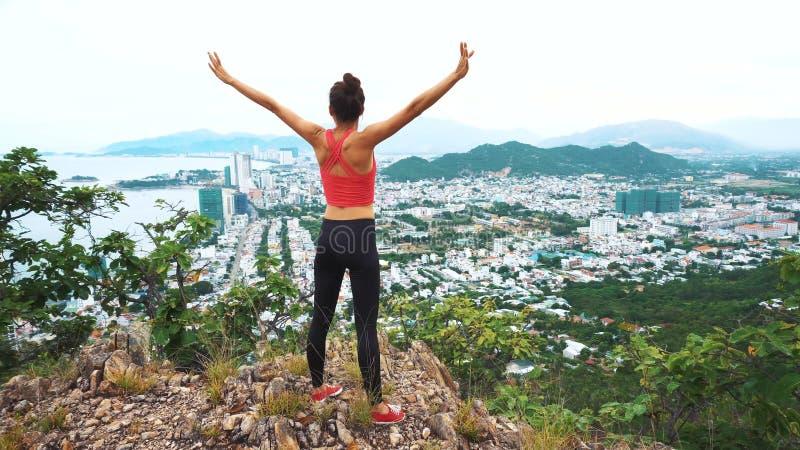 De vrouwenagent heft omhoog handen in de lucht op Wijfje bovenop de berg in werking wordt gesteld, die in het winnen van gebaar t stock foto